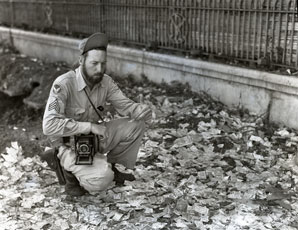[The Photographer Kneels on a Street Littered with Japanese Invasion Money]