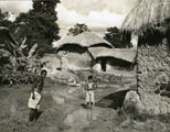 [Village Children Alongside a Wall Plastered with Cow Manure (to be used as Cooking Fuel)]